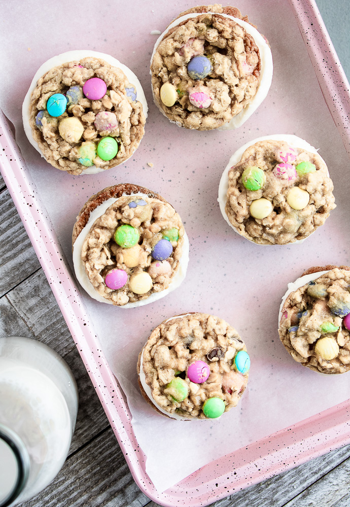 M&M Oatmeal Monster Cookie Sandwiches on a pink baking sheet.
