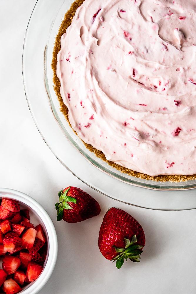 No-bake strawberry cream pie in a pie dish with strawberries.