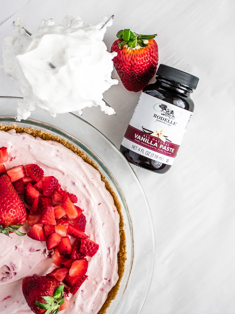 Strawberry cream pie in a pie dish with whipped cream and Rodelle Vanilla Extract sitting next to the dish