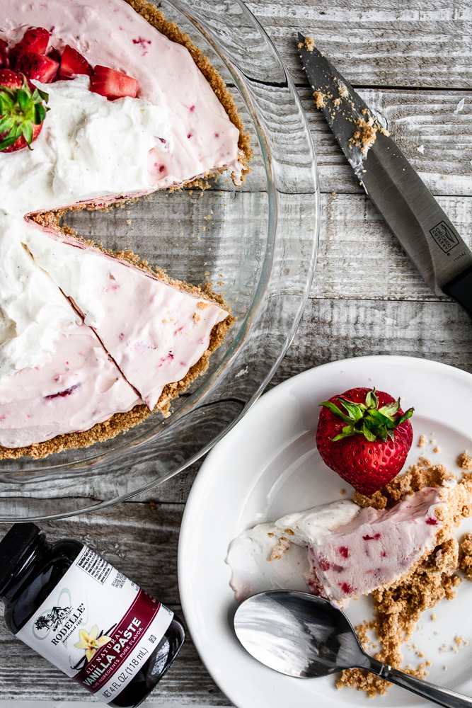 Strawberry cream pie with one slice cut out and placed on a white dish