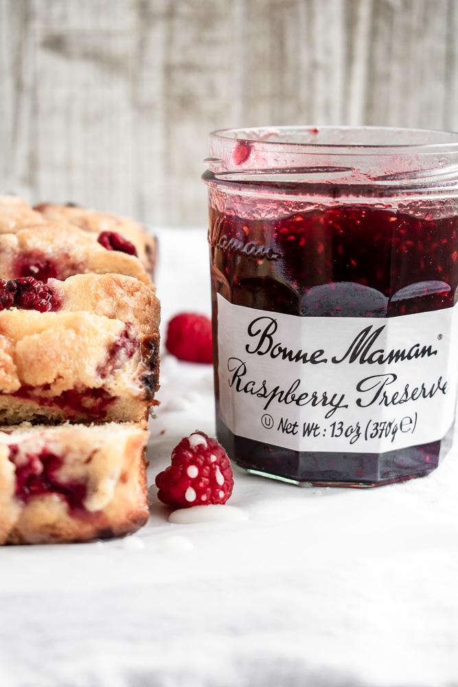 Slices of lemon raspberry swirl cake next to a jar of Bonne Maman Raspberry Jame