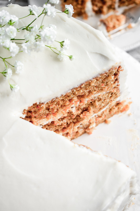 Close up shot of peach carrot cake with a slice taken out of it