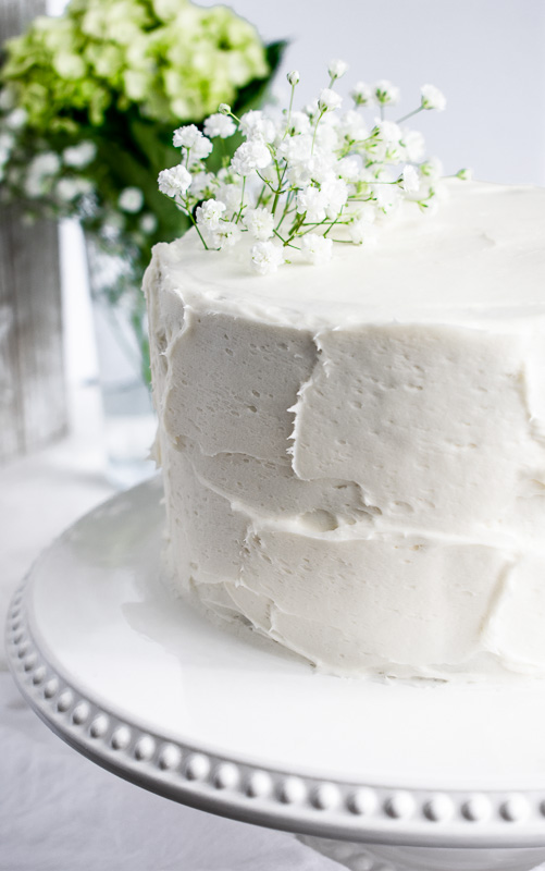 Carrot layer cake on a white cake stand