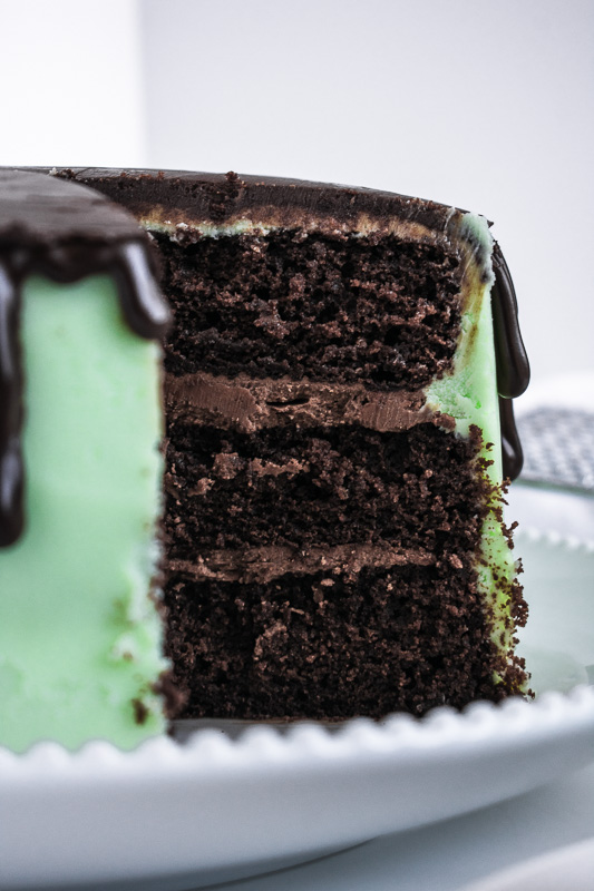 Close up of mint chocolate grasshopper cake on a white plate with slice cut out.