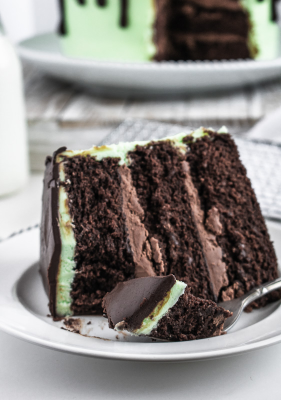 Slice of mint chocolate cake on a white plate with a bit on a fork