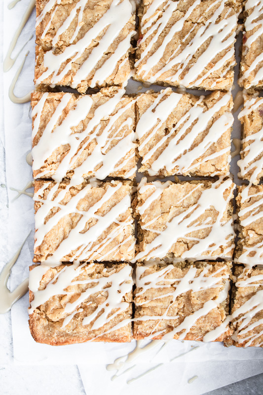Slices of blondies on parchment paper with bourbon glaze drizzled on top