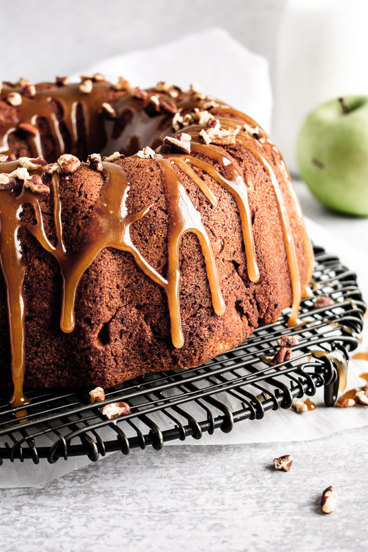 Caramel drizzle dripping down the sides of a caramel apple coffee cake