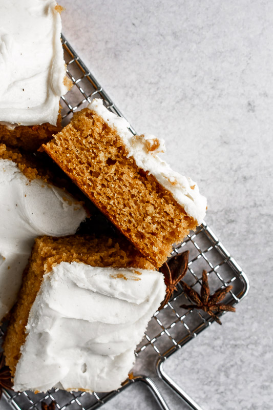 Side view of a pumpkin spice bar with vanilla bean cream cheese frosting on top