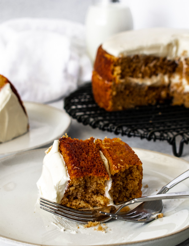 Slice of buttermilk spice cake on a white plate with the whole cake in the background