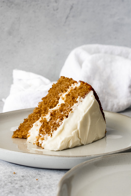 Slice of spice cake with thick maple cream cheese frosting on a white plate