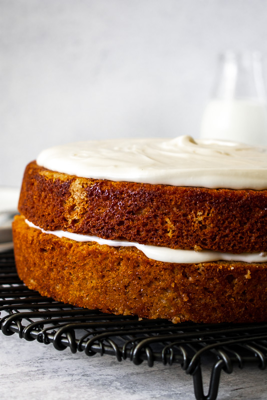 Two layer buttermilk spice cake on a black wire rack