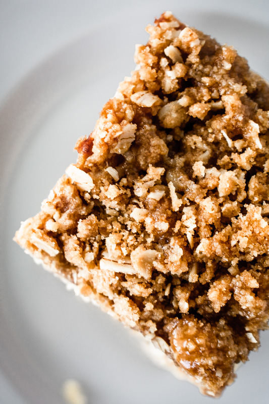 Cinnamon crumble on top of an apple pie bar