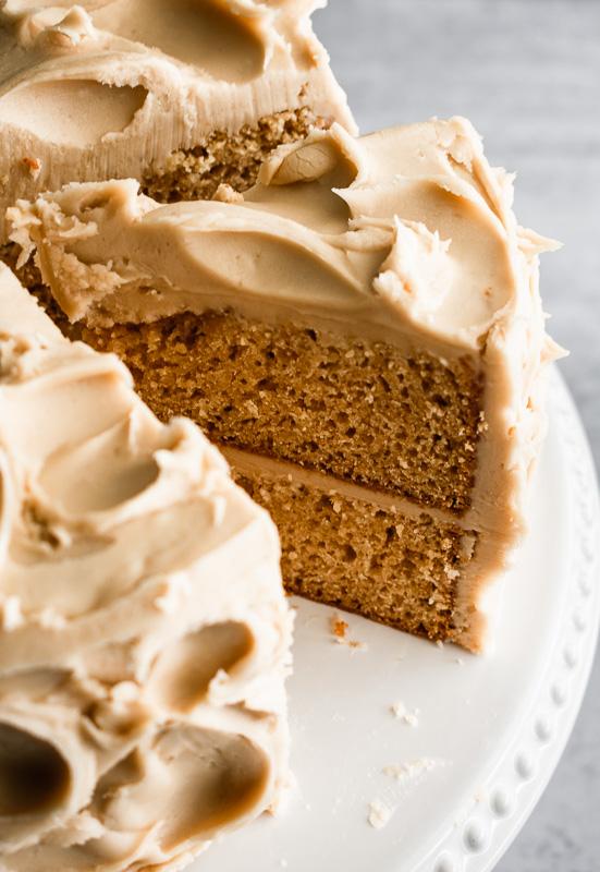 Slice of burnt sugar cake on a white cake platter