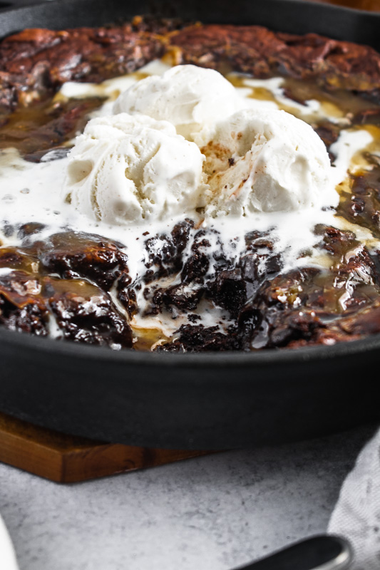Vanilla bean ice cream melting on a warm salted caramel skillet brownie