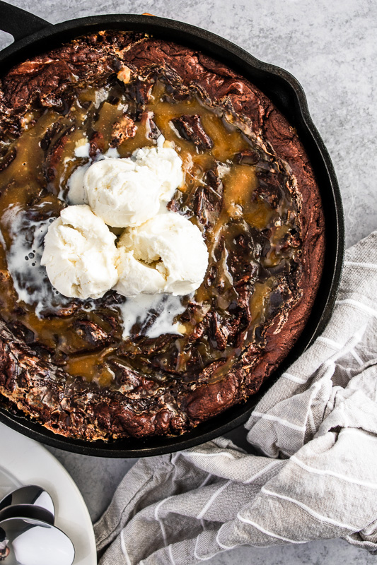 Skillet brownie with salted caramel sauce swirled throughout and vanilla bean ice cream on top