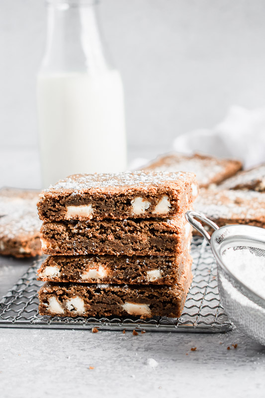 Easy gingerbread blondies stacked on top of each other on a wire rack