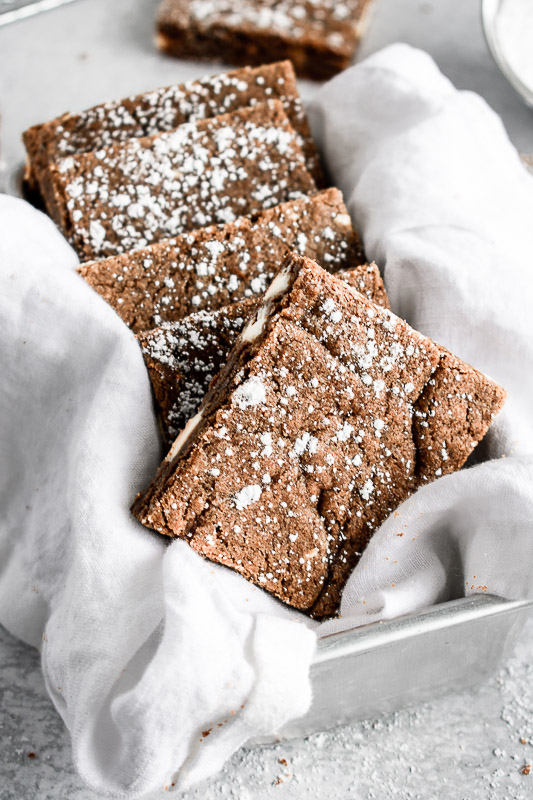 Gingerbread blondies in a metal pan with a white napkin