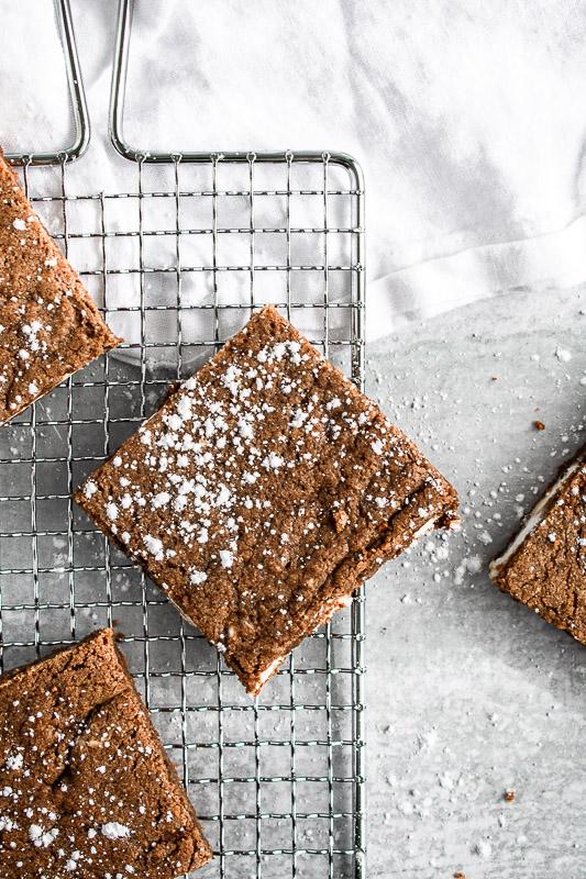 Easy gingerbread blondies with powdered sugar on a metal rack