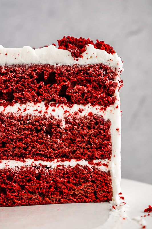 Side view of 3 layer red velvet cake with peppermint cream cheese frosting between layers
