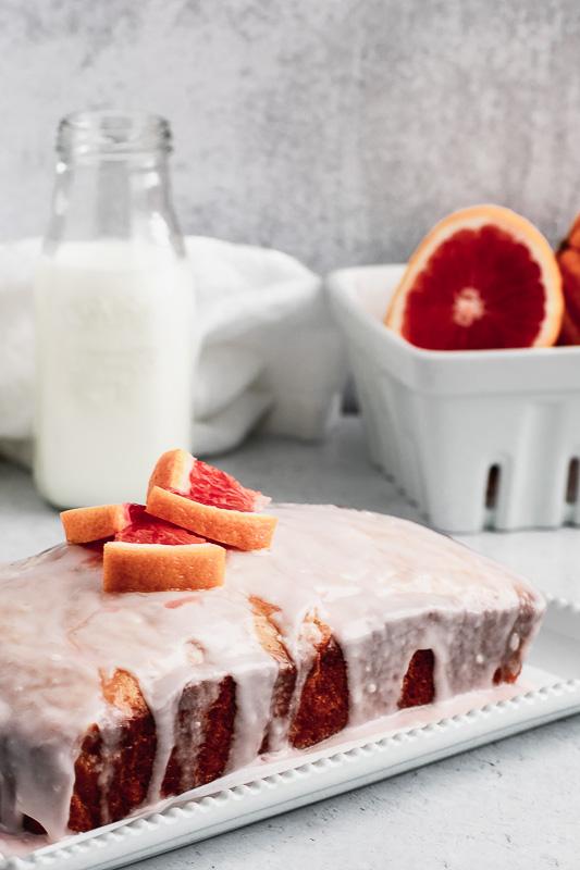 Blood orange loaf cake on a white platter with blood orange glaze