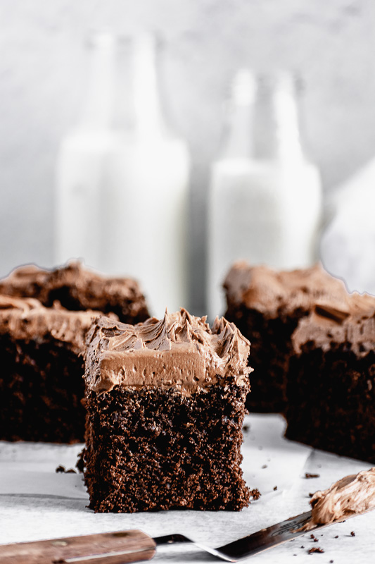 A thick slice of dark chocolate snack cake with dark chocolate buttercream on top