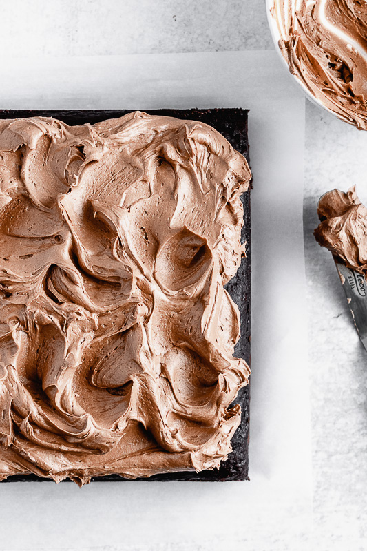 Top view of an 8 inch dark chocolate snack cake covered in dark chocolate buttercream