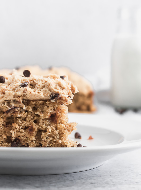 Close up of a slice of oatmeal chocolate chip cookie cake on a white plate