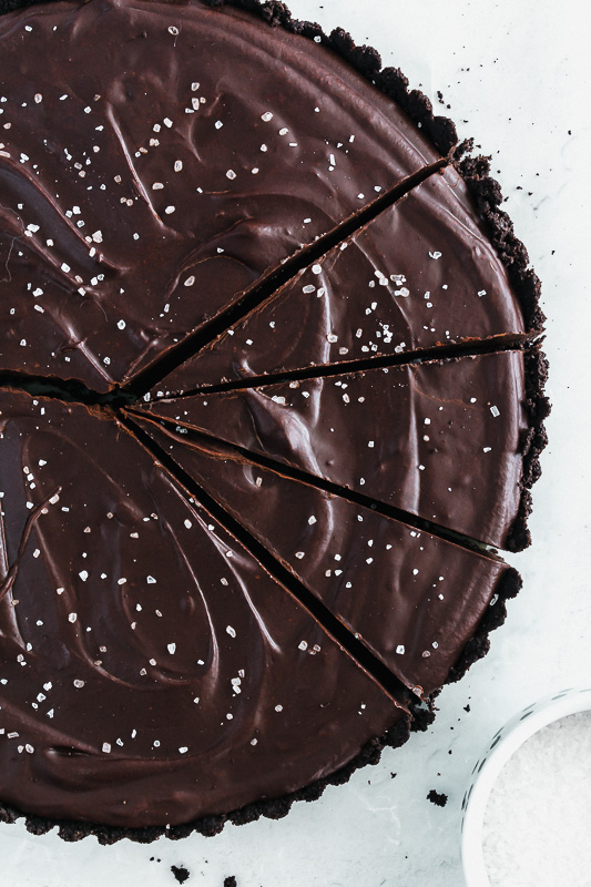 Slices of salted dark chocolate tart on parchment paper