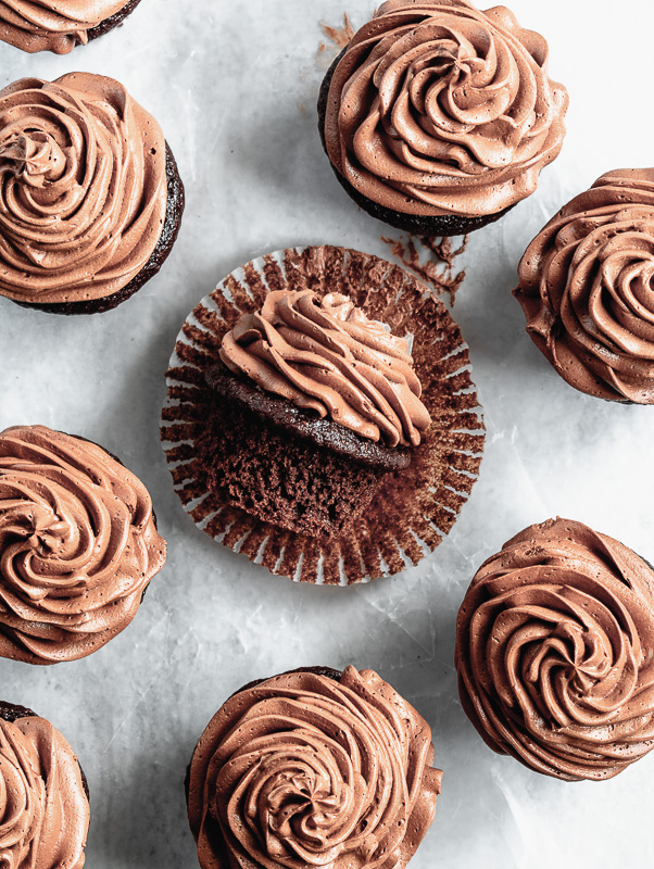 Double dark chocolate cupcake laying on side with cupcake liner removed