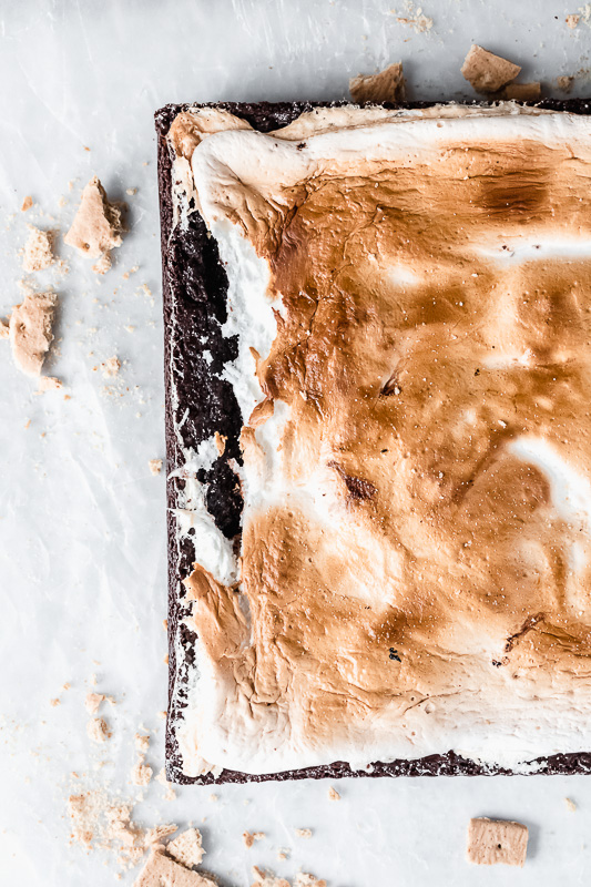 Top view of marshmallow fluff on layered s'mores brownies