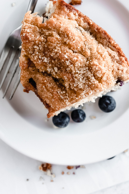 Slice of blueberry muffin cake on a white plate