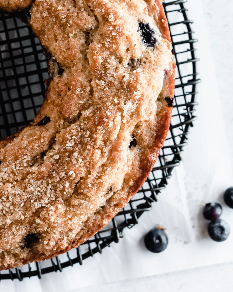 Blueberry muffin cake on a black cooling rack